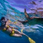 黄色いビキニとウミガメがシュノーケリング